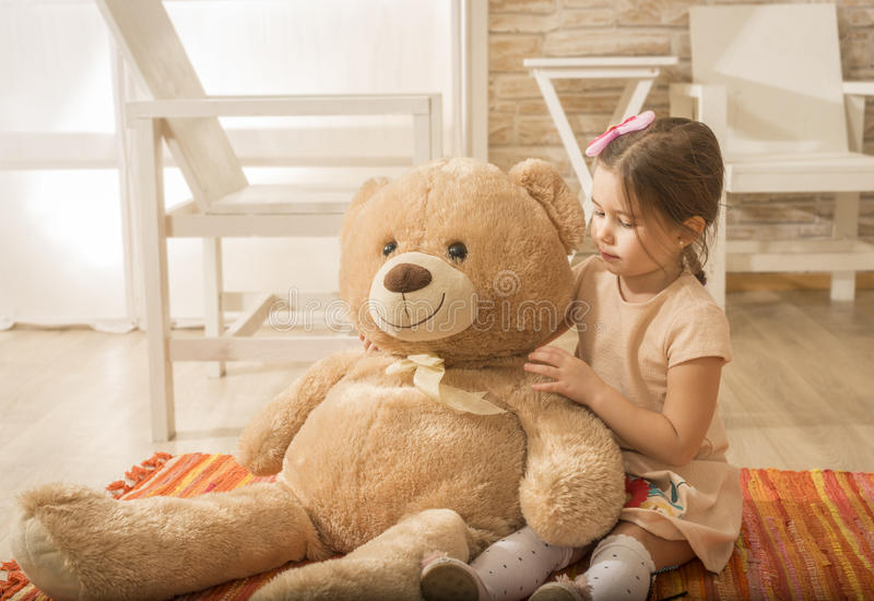 Portrait of expressive charming little girl hugging huge plush bear royalty free stock images