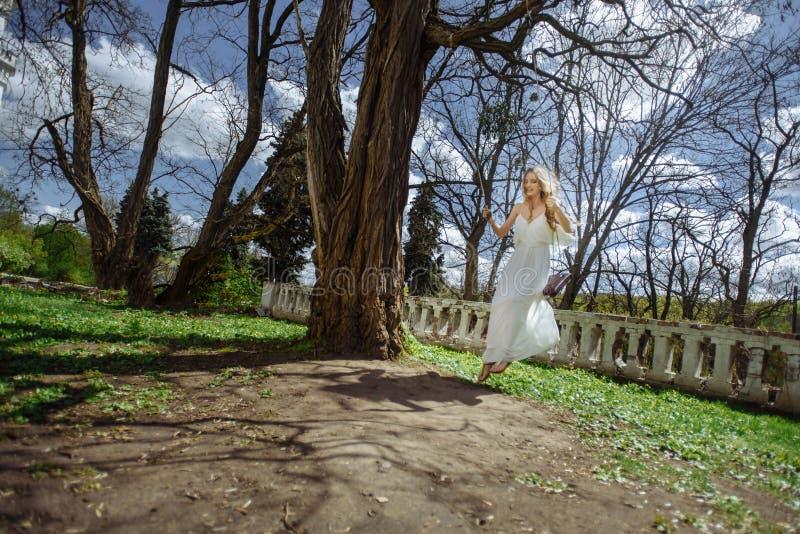 Portrait extérieur d'été de fille assez mignonne de jeunes La belle femme posant sur l'oscillation de conte de fées près marque l photographie stock libre de droits
