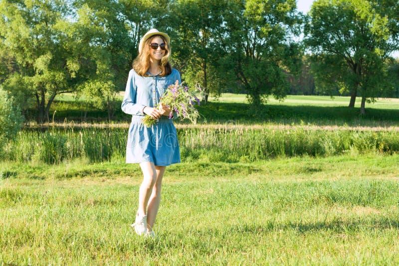 Portrait extérieur d'été de fille de l'adolescence avec le bouquet des wildflowers, chapeau de paille Fond de nature, paysage rur photo libre de droits