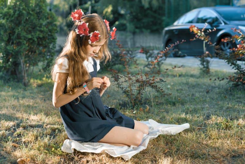 Portrait extérieur d'étudiante élémentaire de fille dans l'uniforme scolaire sur la pelouse avec la guirlande des fleurs roses photo stock