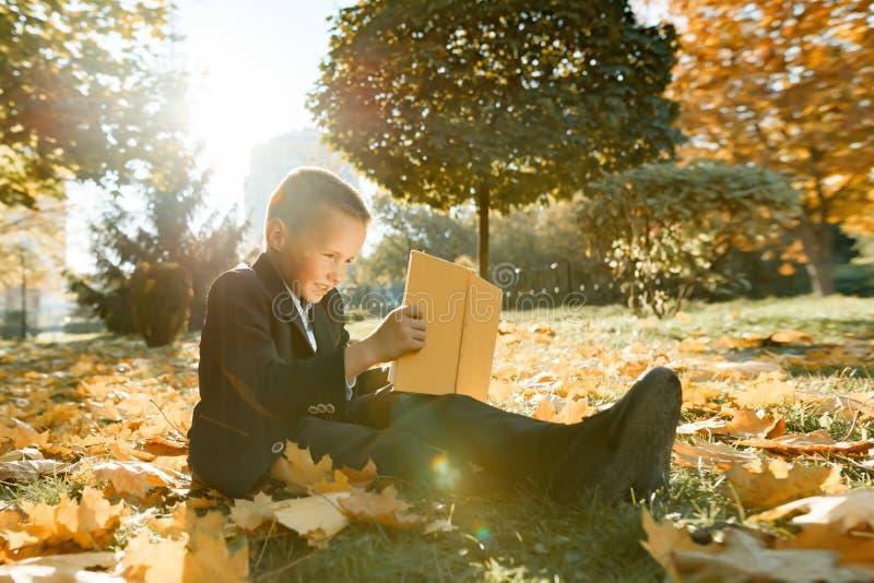 Portrait extérieur d'automne d'un écolier lisant un livre, fond des arbres jaunes en parc, un garçon dans une veste, heure d'or images libres de droits