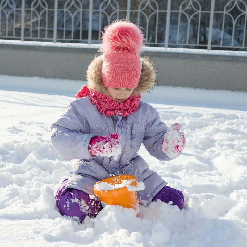 Portrait extérieur d'hiver de fille d'enfant souriant et jouant avec la neige, jour d'hiver ensoleillé lumineux images stock