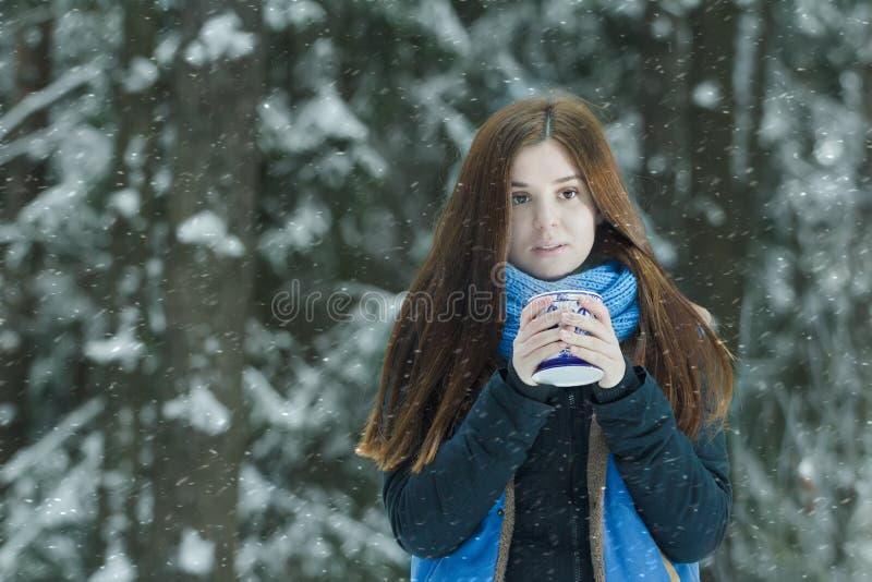 Portrait extérieur d'hiver de geler la jeune dame tenant la tasse avec la boisson chaude pendant les chutes de neige lourdes dans image libre de droits