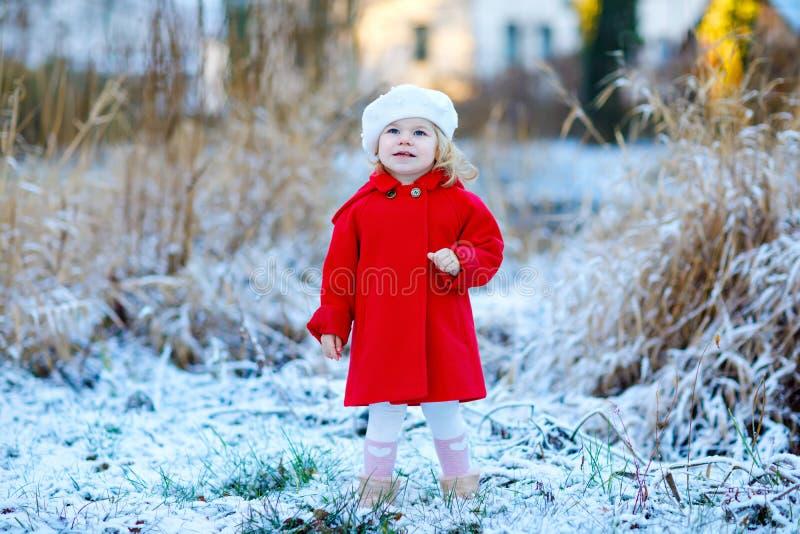 Portrait extérieur d'hiver de peu de fille mignonne d'enfant en bas âge dans le manteau rouge et le barret blanc de chapeau de mo image libre de droits