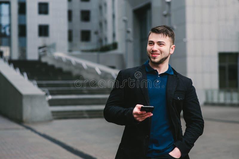 Portrait extérieur d'un jeune homme d'affaires qui véritablement souriant et jugeant un smartphone disponible Concept d'affaires photographie stock libre de droits