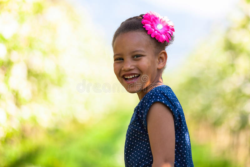 Portrait extérieur d'une jeune fille noire mignonne souriant - pe africain photographie stock