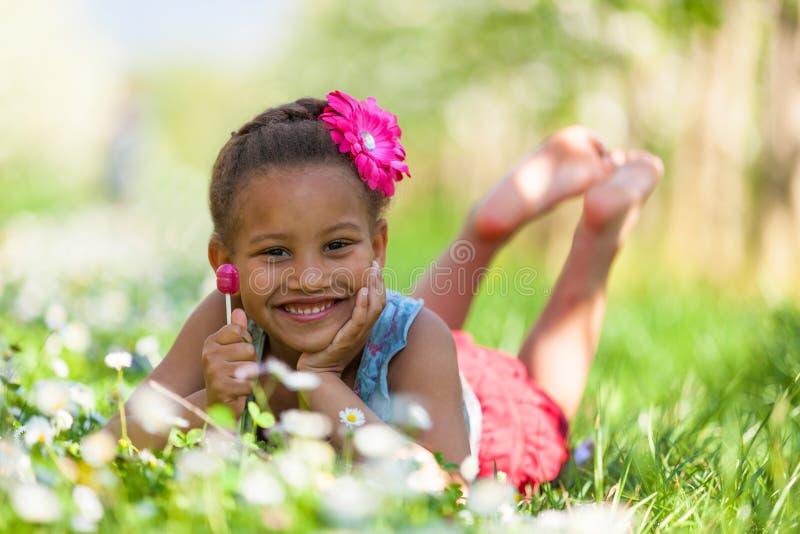 Portrait extérieur d'une jeune fille noire mignonne souriant - pe africain images stock