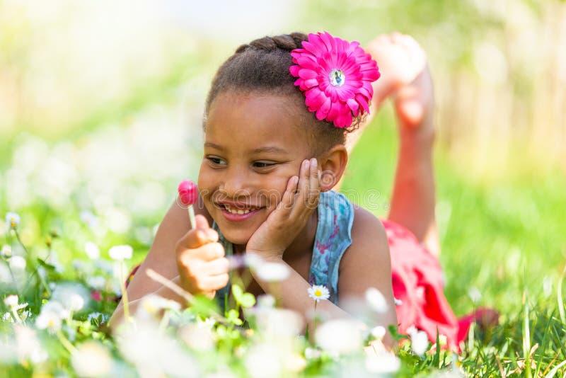Portrait extérieur d'une jeune fille noire mignonne souriant - pe africain photos libres de droits