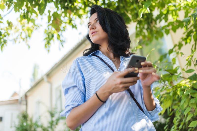 Portrait extérieur de belle brune femelle dans des vêtements sport dans la rue utilisant le téléphone portable, regardant de côté photo libre de droits