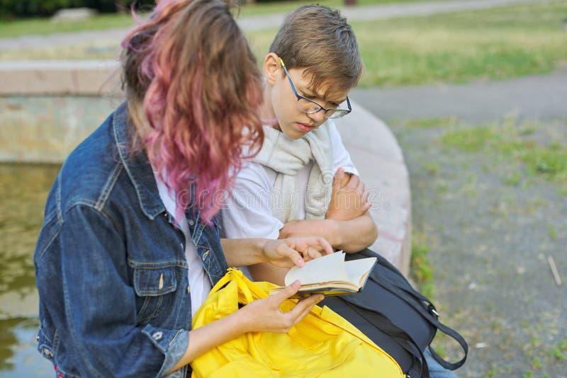 Portrait extérieur de deux étudiants parlants d'adolescents photos stock