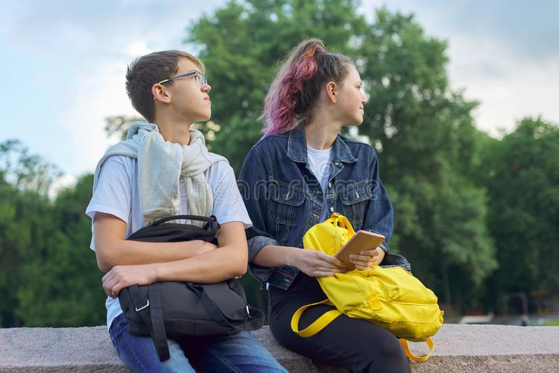 Portrait extérieur de deux adolescents parlants avec le smartphone photo libre de droits