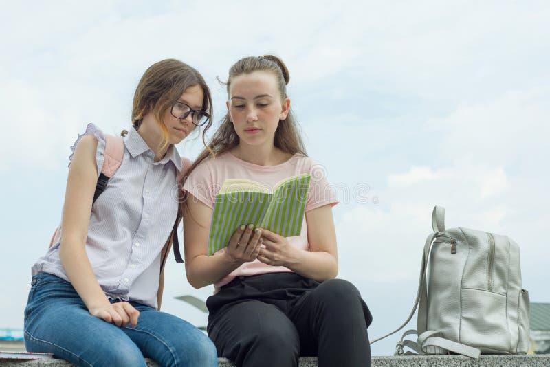 Portrait extérieur de deux jeunes belles étudiantes avec des sacs à dos, livres Filles parler, regardant dans un livre images stock