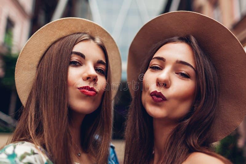 Portrait extérieur de deux jeunes belles femmes à la mode prenant le selfie Filles ayant l'amusement dans la ville Meilleurs amis photo stock