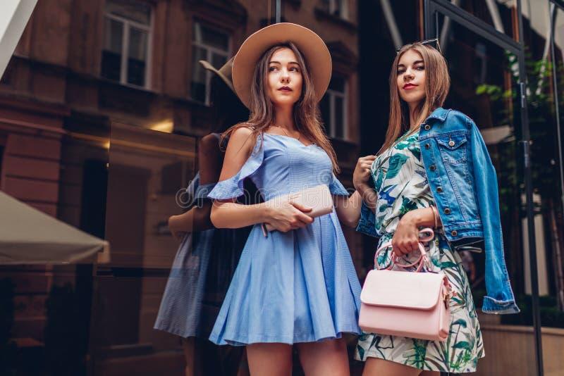 Portrait extérieur de deux jeunes belles femmes Filles utilisant les vêtements et les accessoires élégants dans la ville Meilleur photos libres de droits