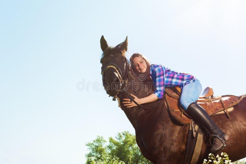 Portrait extérieur de jeune femme étreignant son cheval image stock