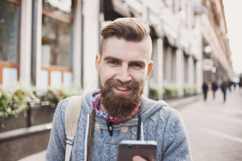 Portrait extérieur de jeune homme moderne avec le téléphone portable dans la rue photographie stock