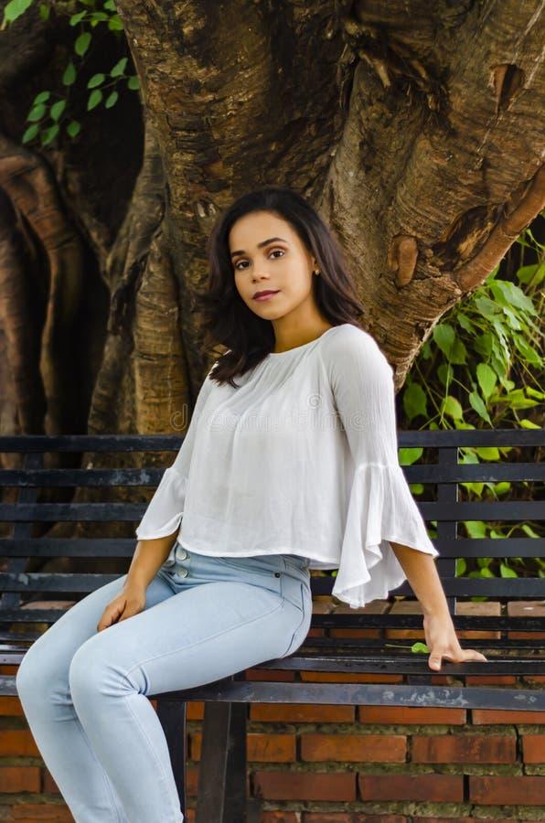 Portrait extérieur de jeunes belles années de la fille 9 à 25 posant dans la rue chemisier blanc de port et jeans et sapatillas s image libre de droits