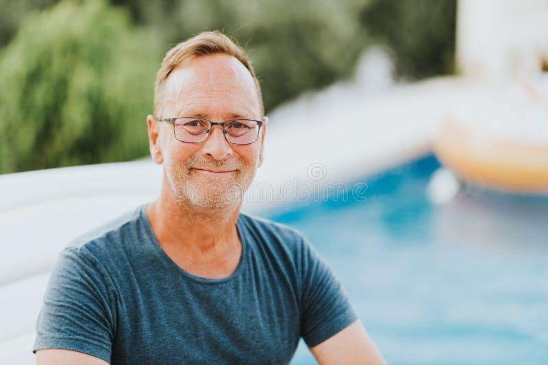 Portrait extérieur de l'homme 50 an se reposant par la piscine photographie stock
