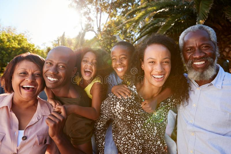 Portrait extérieur de la famille sur plusieurs générations dans le jardin à la maison contre Sun évasé photo libre de droits