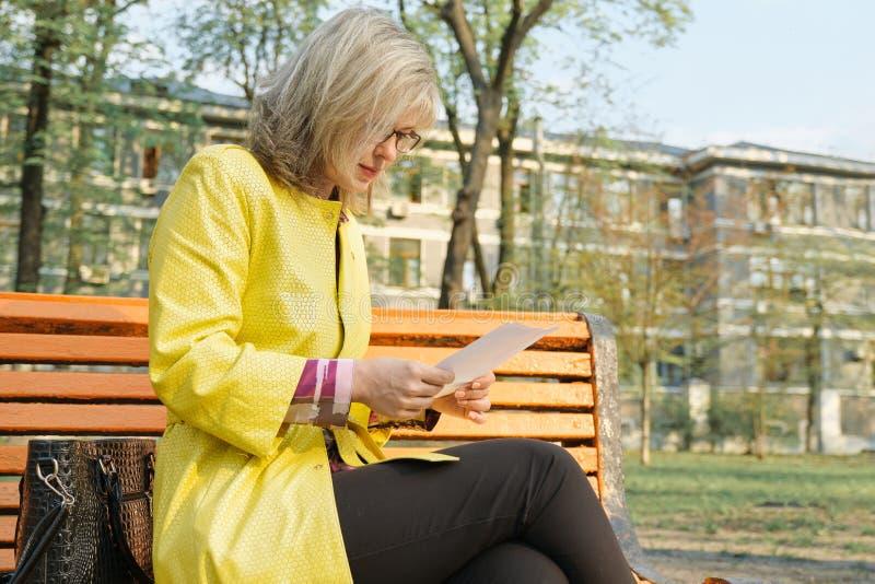 Portrait extérieur de la femme d'affaires mûres avec des verres lisant le papier se reposant sur le parc de banc au printemps photos libres de droits