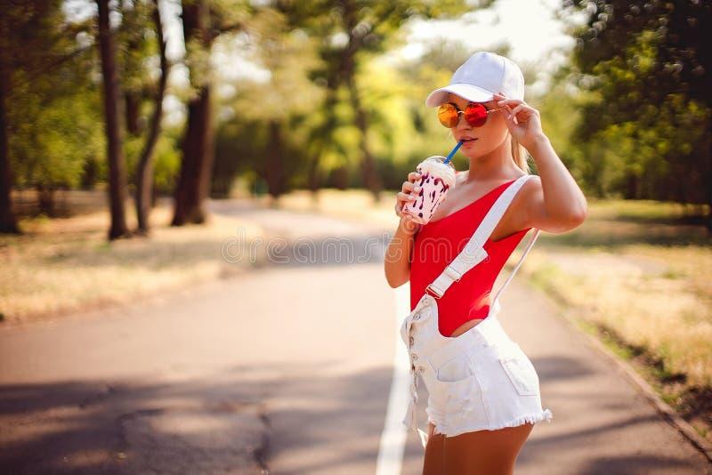 Portrait extérieur de la fille assez élégante de mode ayant le milkshake potable d'amusement photo stock