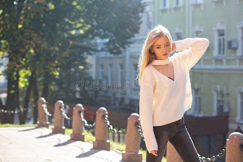 Portrait extérieur de modèle élégant utilisant l'équipement élégant posant à la rue avec la lumière naturelle du soleil L'espace  photo stock