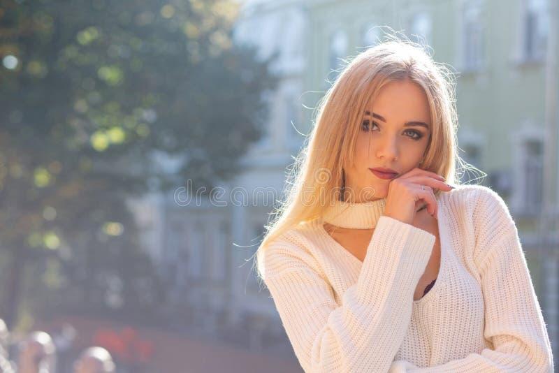 Portrait extérieur de modèle fascinant utilisant l'équipement élégant posant à la rue avec la lumière naturelle du soleil L'espac photos libres de droits