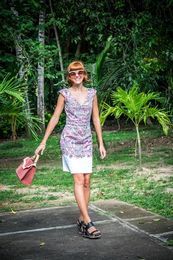 Portrait extérieur de mode dame élégante sensuelle de charme de jeune dans des lunettes de soleil avec le sac fait main de luxe d image libre de droits