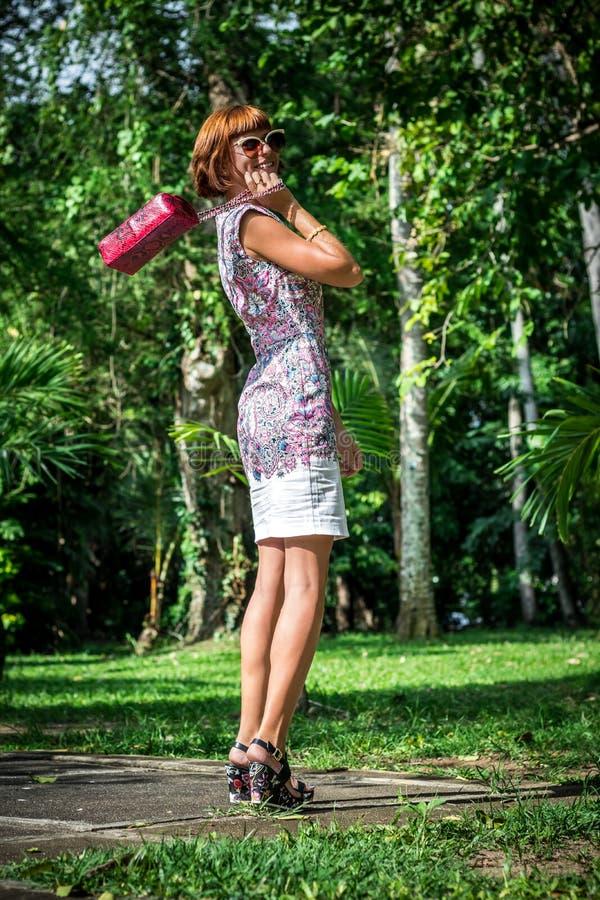 Portrait extérieur de mode dame élégante sensuelle de charme de jeune dans des lunettes de soleil avec le sac fait main de luxe d photographie stock