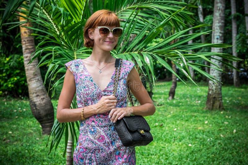 Portrait extérieur de mode dame élégante sensuelle de charme de jeune dans des lunettes de soleil avec le sac fait main de luxe d photos libres de droits