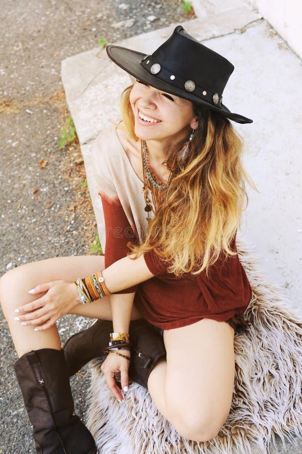 Portrait extérieur de mode de la jeune belle femme s'asseyant sur une fourrure et souriant, chapeau sur une tête photographie stock