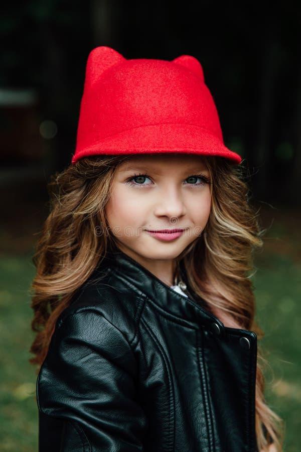 Portrait extérieur de mode de vie d'adolescente élégante de petite fille sur le parc de ville Bel enfant, portant photos libres de droits