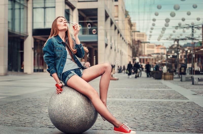 Portrait ext?rieur de mode de vie de jolie bulle de soufflement de jeune fille dans la ville, portant ? l'arri?re-plan urbain de  images libres de droits