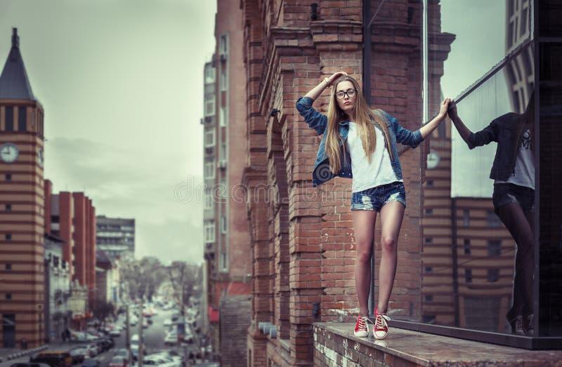 Portrait extérieur de mode de vie de jolie jeune fille, allant au bord du haut parapet de construction, robe de port de butin de  image libre de droits