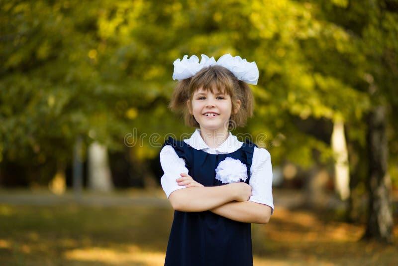 Portrait extérieur de petite écolière heureuse dans l'uniforme scolaire en parc image stock