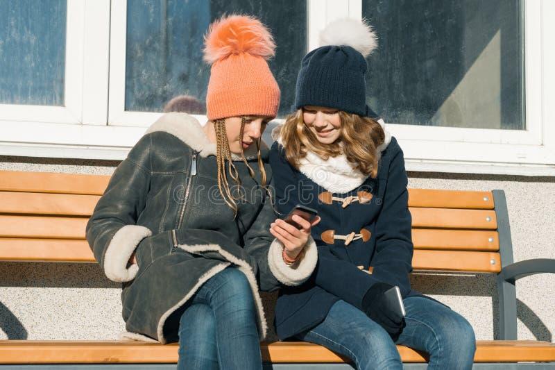 Portrait extérieur en gros plan d'hiver de deux étudiants d'adolescentes dans le profil souriant et parlant, filles regardant le  images libres de droits