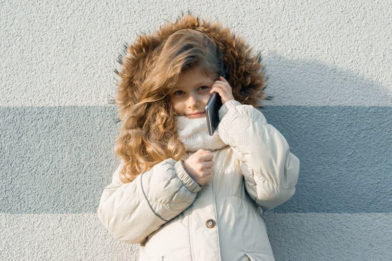 Portrait extérieur en gros plan d'hiver de l'enfant, fille blonde avec les cheveux bouclés de 7, 8 ans dans le capot de fourrure, images stock