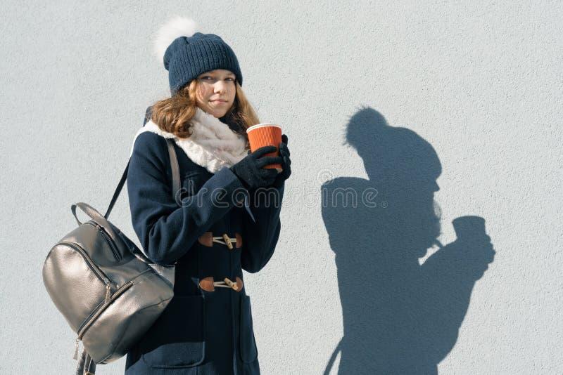 Portrait extérieur ensoleillé d'hiver d'adolescente portant un manteau et tricoter le chapeau avec la tasse de la boisson chaude, photo libre de droits