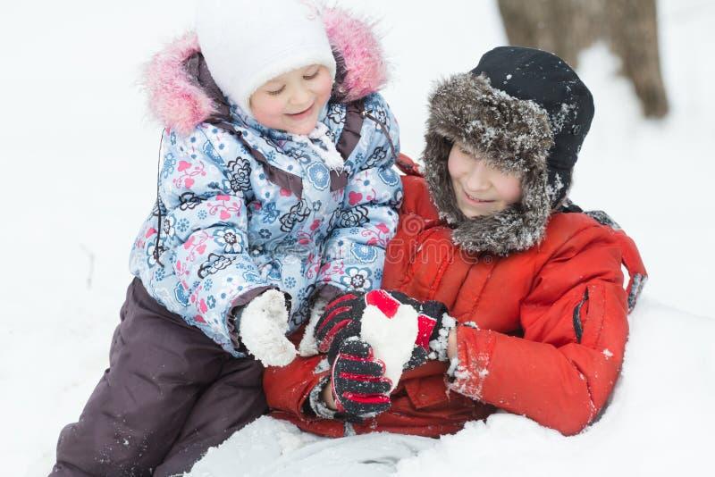 Portrait extérieur givré de deux enfants de mêmes parents jouants en congère d'hiver avec le chiffre en forme de coeur de neige photographie stock