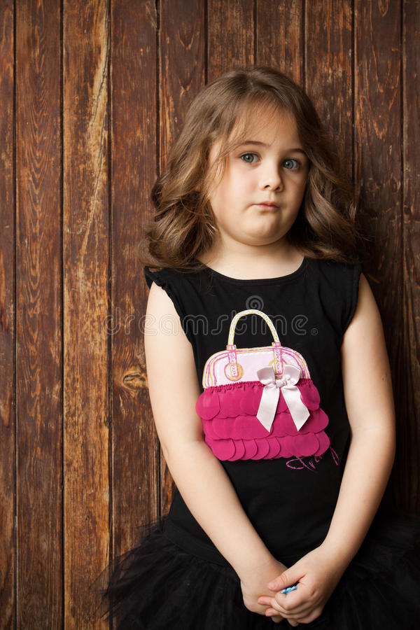 Portrait extérieur porte en bois debout mignonne de petite fille d'une prochaine image stock