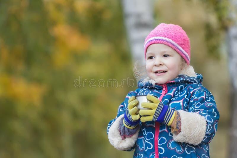 Portrait extérieur principal d'automne et d'épaules de petite fille tenant la tasse en acier de flacon de thermos dans des mains photos libres de droits