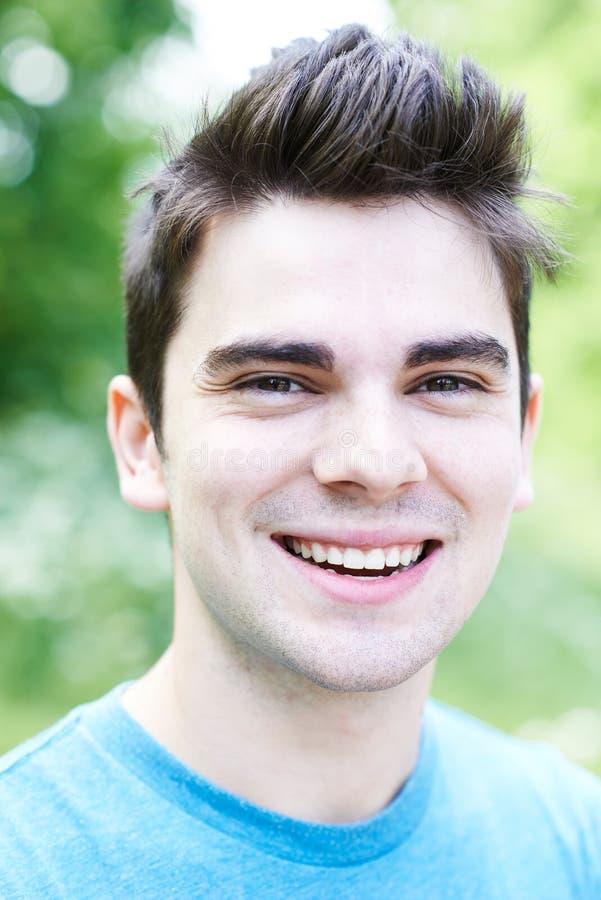 Portrait extérieur principal et d'épaules de jeune homme de sourire images libres de droits