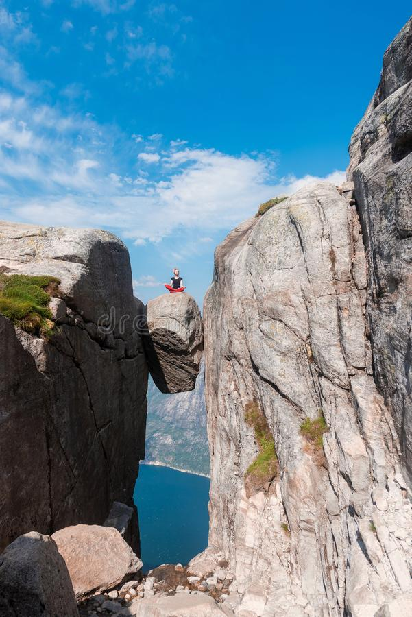 Portrait of a extreme plan travel for the girl on the stone of the kjerag in the mountains of Norway, the feeling of royalty free stock images