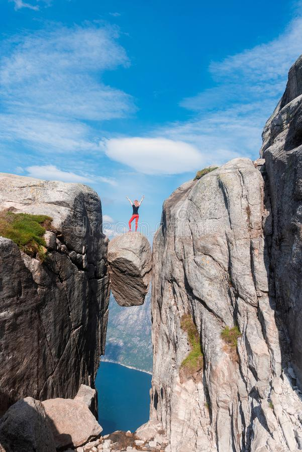 Portrait of a extreme plan travel for the girl on the stone of the kjerag in the mountains of Norway, the feeling of royalty free stock photography