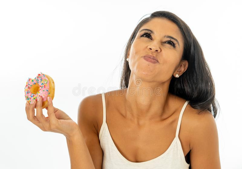 Portrait of extremely happy beautiful latin young woman eating a delicious donuts enjoying it with pleasure in give yourself a royalty free stock images