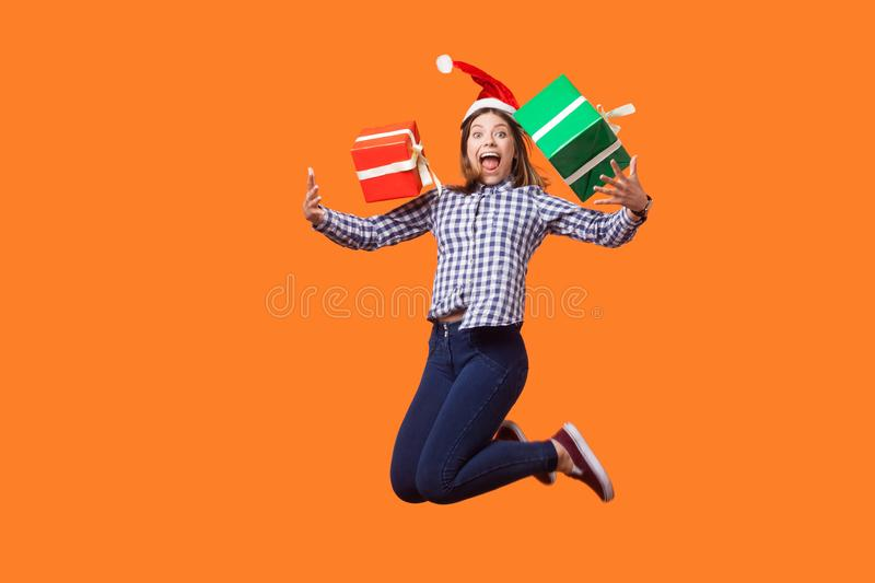 Portrait of extremely happy brunette woman in santa hat and checkered shirt jumping for joy, flying with wrapped xmas gift boxes, royalty free stock photo