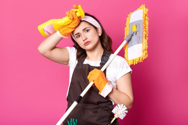 Portrait exuasted housewife tired of housework, wears white t shirt, brown apron, hairband, orange gloves  over pink stock image