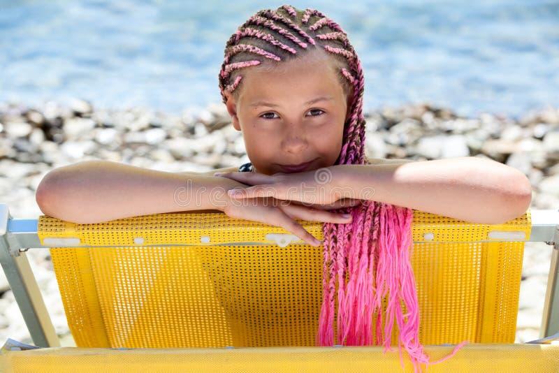 Portrait facial de fille caucasienne de la préadolescence avec la coiffure rose de dreadlocks regardant du canapé jaune du soleil photo libre de droits