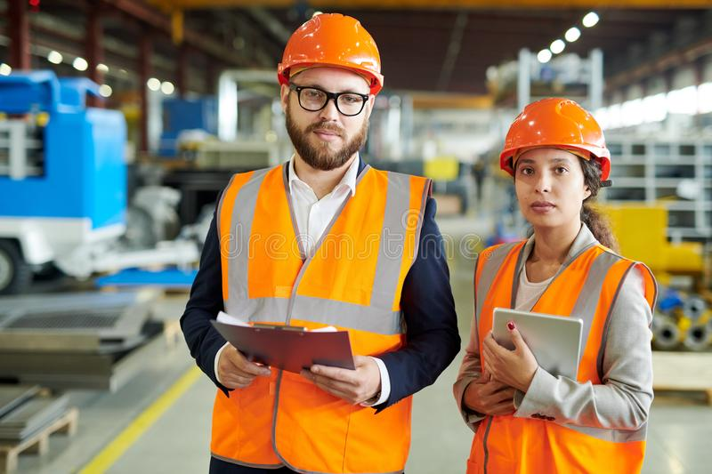 Portrait of Factory Employees. Waist up portrait of two modern factory workers wearing hardhats and reflective vests posing in production workshop, holding stock photography