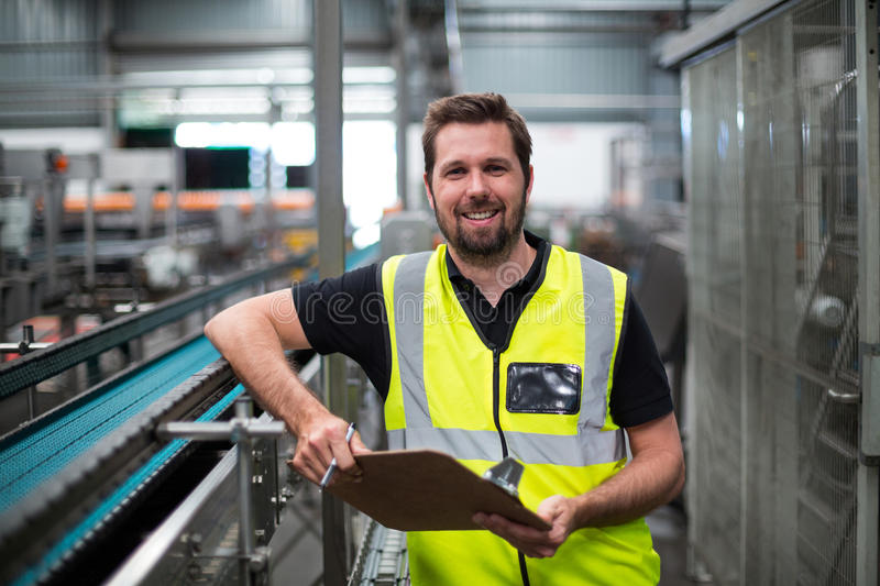 Portrait of factory worker standing with clipboard stock image